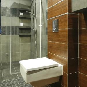 Aby, wizualnie poszerzyć wąską łazienkę płytki imitujące kamień ułożono poziomo.Efekt szerokich pasów na ścianie i podłodze dodatkowo wzmacniają aluminiowe listwy, które wypełniły fugi. Projekt: Marta Kilan. Fot. Bartosz Jarosz.