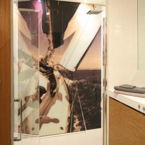 Kabina prysznicowa zajmuje wnękę przy jednej z krótszych ścian. Fototapeta na ścianie to nadruk na szkle. Zamiast brodzika, w podłodze zainstalowano odpływ wykończony płytkami, jak reszta podłogi. Projekt: Małgorzata Galewska. Fot. Bartosz Jarosz.
