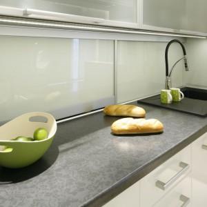 Przestrzeń nad blatem można wykorzystać jako dodatkowe miejsce przechowywania. Za szklanymi przesuwnymi drzwiczkami ukryto schowek, w którym znalazła się między innymi kuchenka mikrofalowa. Projekt: Marta Kilan. Fot. Bartosz Jarosz.