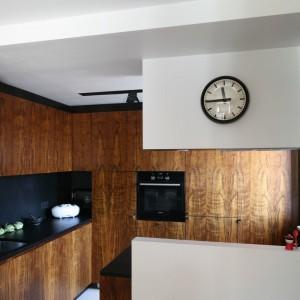 Kuchnia urządzona w amerykańskim minimalizmie w stylu lat 50-tych. Fornirowana zabudowa została przełamana czarną enklawą, którą tworzy blat wraz ze ścianą nad nim. Obie powierzchnie wykończono czarnym grafitem. Projekt: Kasia i Michał Dudko. Fot. Bartosz Jarosz.