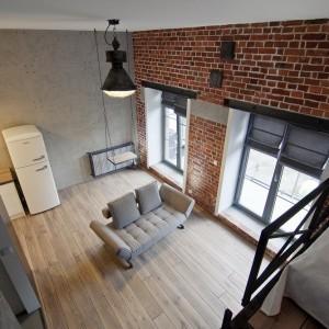 Salon - jak w prawdziwym lofcie przystało - wieńczy wysoki sufit. Przestrzeń wykorzystano na stworzenie antresoli, która stała się kącikiem sypialnianym. Fot. RED Real Estate Development.