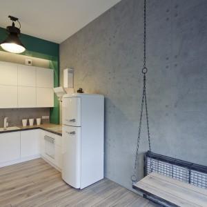 W kuchni postawiono na białą zabudowę, ożywioną delikatnie turkusowym akcentem. Designerskim detalem jest lodówka w stylu retro w miętowym kolorze. Fot. RED Real Estate Development.