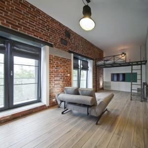 Meblościankę z panelem TV wpasowano w przestrzeń pod antresolą. Biała zabudowa, okraszona turkusowym akcentem, estetycznie chowa się pod schodami. Fot. RED Real Estate Development.