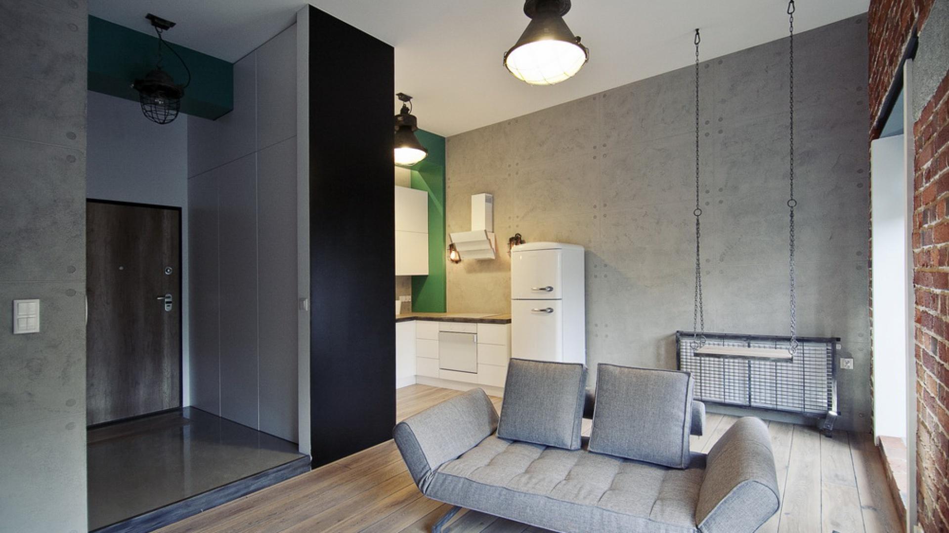 Ścianę spajającą przestrzeń kuchni z salonem wykończono dekoracyjnym betonem. Jego chłodna szarości kontrastuje z czerwoną cegłą na prostopadłej powierzchni. Fot. RED Real Estate Development.