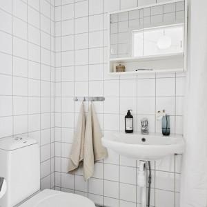Ściany w łazience wykończono białymi płytkami, a jedynym ciemnym akcentem jest szara podłoga. To jedyne pomieszczenie w całym mieszkaniu, w którym biel nie wkroczyła również w płaszczyznę podłogi. Jest to rozwiązanie praktyczne, z uwagi na charakter pomieszczenia, w którym podłoga często ulega zabrudzeniom. Fot. Stadshem.se/Janne Olander.