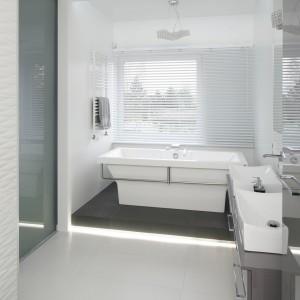 W nowoczesnej łazience modną szarość przełamuje biała armatura. Geometryczne kształty umywalki, wanny czy bidetu podkreślają minimalistyczny styl wnętrza. Projekt: Katarzyna Mikulska-Sękalska. Fot. Bartosz Jarosz.