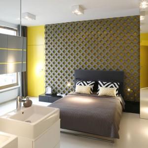 W centralnym miejscu pomieszczenia ustawiono nowoczesne łóżko z tapicerowanym zagłówkiem. Ścianę, przy której je ustawiono wykończono ażurowymi panelami, które wnoszą do aranżacji swoistą finezję. Projekt: Monika i Adam Bronikowscy. Fot. Bartosz Jarosz.