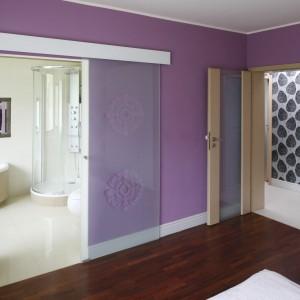 Jasna łazienka z prysznicem jest nieodłączną częścią sypialni. Rolę granicy między dwoma pomieszczeniami pełnią szklane drzwi przesuwne z subtelnym wzorem. Projekt: Beata Ignasiak. Fot. Bartosz Jarosz.