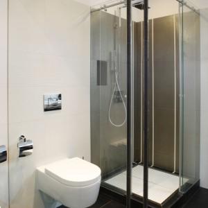Podobnie jak w sypialni, również i w łazience króluje czerń - na podłodze oraz biel - na ścianach. Duża ilość szkła nadaje wnętrzu minimalistyczny wygląd. Projekt: Dąbrówka Potowska. Fot. Bartosz Jarosz.