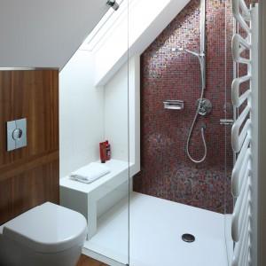 W sąsiadującej łazience dominuje to samo drewno, co w sypialni. Ścianę za prysznicem wykończono mozaiką w ciepłym odcieniu bakłażanu. Projekt: Magdalena Konopka, Marcin Konopka. Fot. Bartosz Jarosz.