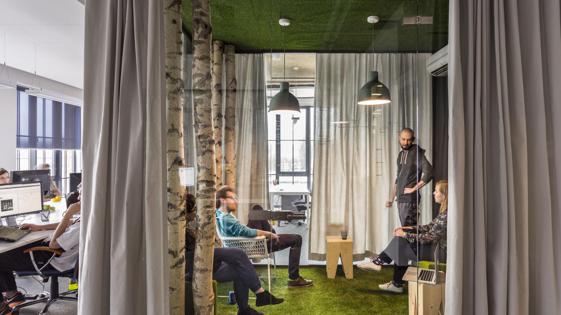 W kontraście dla surowego tła, wprowadzono akcenty bardzo naturalne i kojarzące się z odpoczynkiem, w postaci prawdziwych pni brzóz, drewnianych mebli wykonanych ze sklejki brzozowej, oraz sztucznej trawy, przekornie ułożonej na ścianach i sufitach. Fot. Libido Architekci