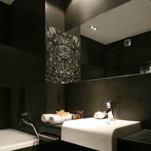 W pomieszczeniu zdominowanym przez wizualnie ciężki oraz ciemny materiał, jakim jest bazalt, ważną rolę pełnią także lustra, które powiększają łazienkę i dają wrażenie głębi. Fot. Bartosz Jarosz.