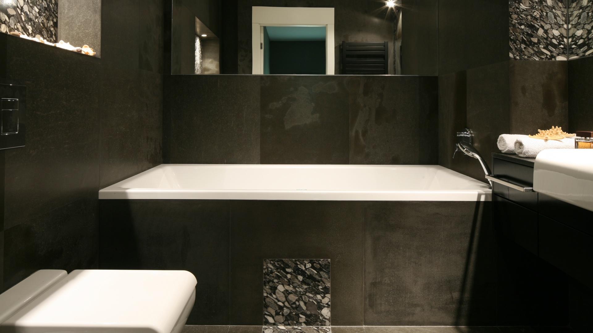 Aranżację łazienki zdominował kamień naturalny. Okładziny wykonane zostały z bazaltowych płyt. Lustro nad wanną dodaje wnętrzu głębi. Fot. Bartosz Jarosz.