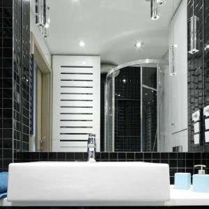 Lustro odpowiada szerokości strefy umywalki i sięga aż do sufitu zapewniając wrażenie głębi. Połyskująca powierzchnia mozaiki odbija światło dodając wizualnej przestrzenie niewielkiej łazience. Projekt: Marta Kilan. Fot. Bartosz Jarosz.