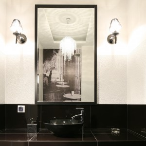 W pionowym lustrze efektownie odbija się nie tylko umieszczona na przeciwległej ścianie fototapeta, ale także elegancki żyrandol dodając łazience szyku i optycznej przestrzeni. Projekt: Karolina i Artur Urban. Fot. Bartosz Jarosz.
