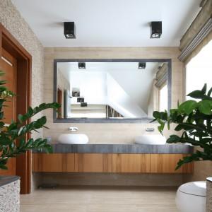 Duże lustro z opaską wykonaną z kamienia naturalnego zapewnia łazience niezwykły efekt głębi. Jest też niewątpliwą dekoracją. Projekt: Karolina Łuczyńska. Fot. Bartosz Jarosz.