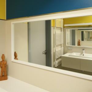W tej łazience lustra wprawione w proste białe ramy umieszczone zostały naprzeciw siebie co dało niezwykły efekt lustra w lustrze dodając przy tym głębi pomieszczeniu. Projekt: Konrad Grodziński. Fot. Bartosz Jarosz.