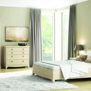 Sypialnia Gusta marki Paged Meble to komfortowe łóżko, stoliki nocne, komoda z szufladami oraz szafa trzydrzwiowa z lustrem. Jasne drewno sprawia, że eleganckie meble wyglądają lekko. Kolekcja projektu Roberta Kowalczyka. Fot. Paged Meble.