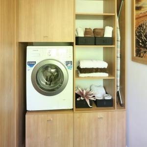 W pralni wygospodarowanej z przestrzeni łazienki zmontowano praktyczną zabudowę: z pralką na wygodnej wysokości, miejscem na detergenty, zapasowe ręczniki a nawet deskę do prasowania. Proj. Małgorzata Błaszczak. Fot. Bartosz Jarosz.