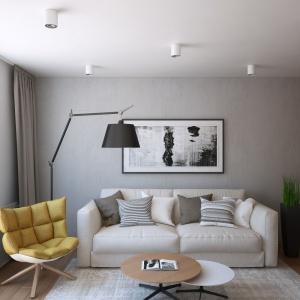 Ścianę bezpośrednio za sofą wykończono tynkiem z efektem betonu, który wprowadza delikatnie surowszy klimat do wnętrza. Z fakturą betonu pięknie kontrastuje fornir na prostopadłej ścianie. Projekt i wizualizacje: Geometrium Design Studio.