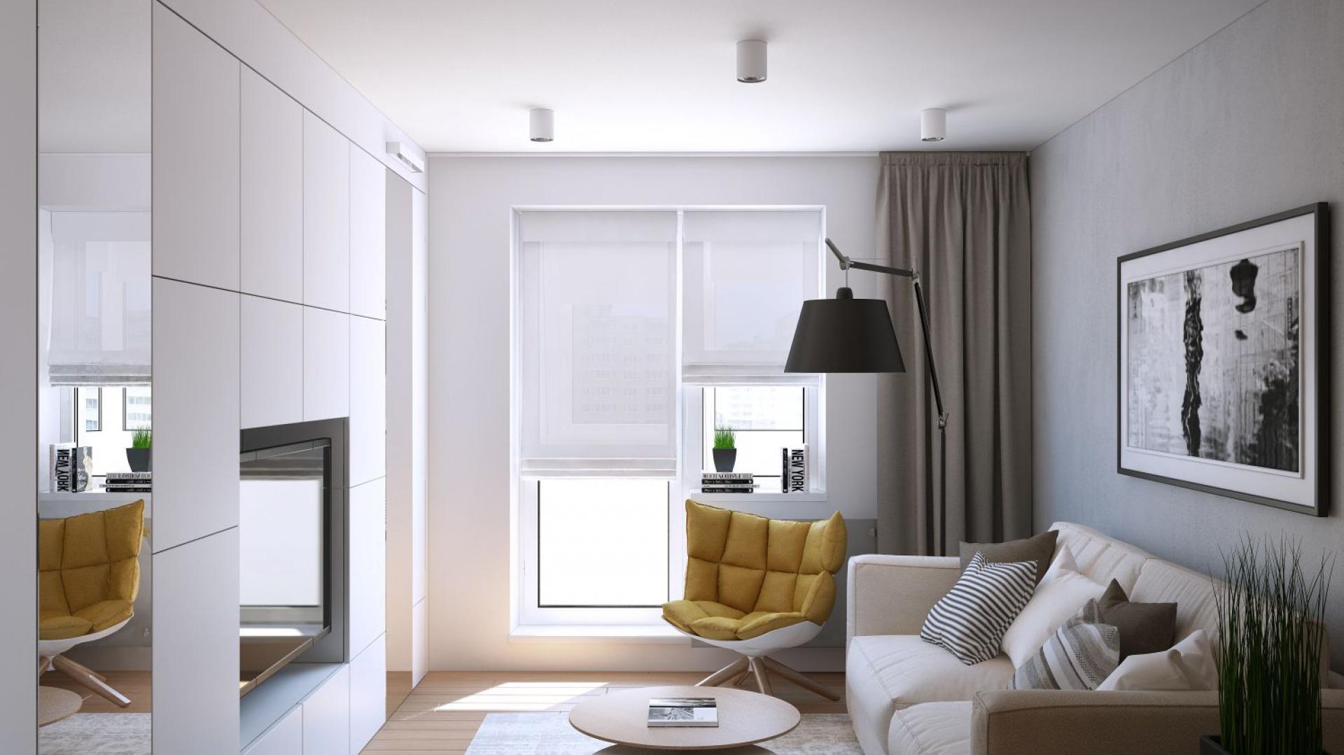 W jednym pomieszczeniu połączono funkcję pokoju dziennego i sypialni. Jest tutaj miejsce na wypoczynek (sofa z funkcją spania), dwa duże lustra, powiększające optycznie wnętrze i pozwalające właścicielce ćwiczyć jogę oraz ściana z pojemną zabudową i TV. Projekt i wizualizacje: Geometrium Design Studio.