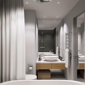 W łazience postawiono na ciemniejszą tonację kolorów, obecnych w innych pomieszczeniach. Ściany wykończono naturalnym kamieniem w antracytowym kolorze. Projekt i wizualizacje: Geometrium Design Studio.