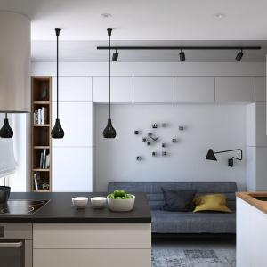 Nad niewielkim półwyspem zawisły trzy czarne, dekoracyjne lampy. Paleta kolorów we wnętrzu to biel, szarości i beże z brązami, a obecność czarnych detali dodaje mu charakteru. Projekt i wizualizacje: Geometrium Design Studio.