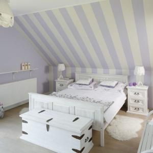 Urządzona pod skosami sypialnia to prywatne królestwo pani i pana domu. Miejsce tu odnalazły białe stylizowane meble. Na tle lawendowej ściany prezentują się niezwykle dostojnie. Projekt Beata Ignasiak. Fot. Bartosz Jarosz.