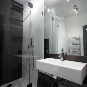 W drugiej łazience postawiono na uniwersalne połączenie ciemnych szarości i bieli. Jest elegancko i bardzo minimalistycznie. Projekt i zdjęcia: Soma Architekci.