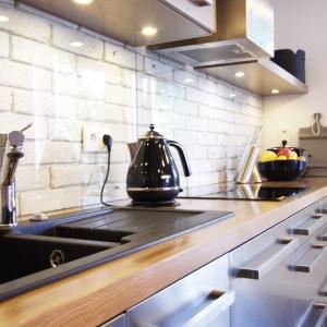 Ściany w kuchni wyłożono białą cegłą, łączącą w sobie dwa style, których fanami są właściciele mieszkania. Jej chropowata, surowa faktura wpisuje się w estetykę loftową, z kolei biała barwa przywodzi na myśl stare, kamieniczne mieszkania. Projekt i zdjęcia: Soma Architekci.
