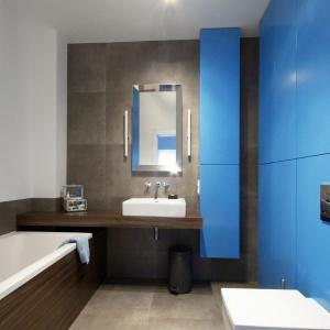 W przestrzeni łazienki króluje beton, ocieplony delikatnie zabudową wanny i minimalistyczną półką podumywalkową w kolorze drewna. Projekt i zdjęcia: Soma Architekci.
