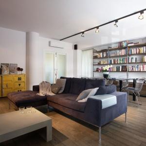 Drewniana podłoga wykonana z postarzanych desek funkcjonuje jako element spajający wizualnie całe mieszkanie. Jednocześnie idealnie harmonizuje ona z meblami w industrialnym stylu. Projekt i zdjęcia: Soma Architekci.