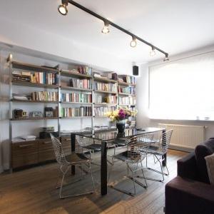 Widoczne stalowe elementy konstrukcji regału z biblioteczką nadają salonowi surowy, lloftowy charakter, potęgowany przez szlifowane betonowe płyty na ścianie, widoczne za otwartymi półkami. Projekt i zdjęcia: Soma Architekci.