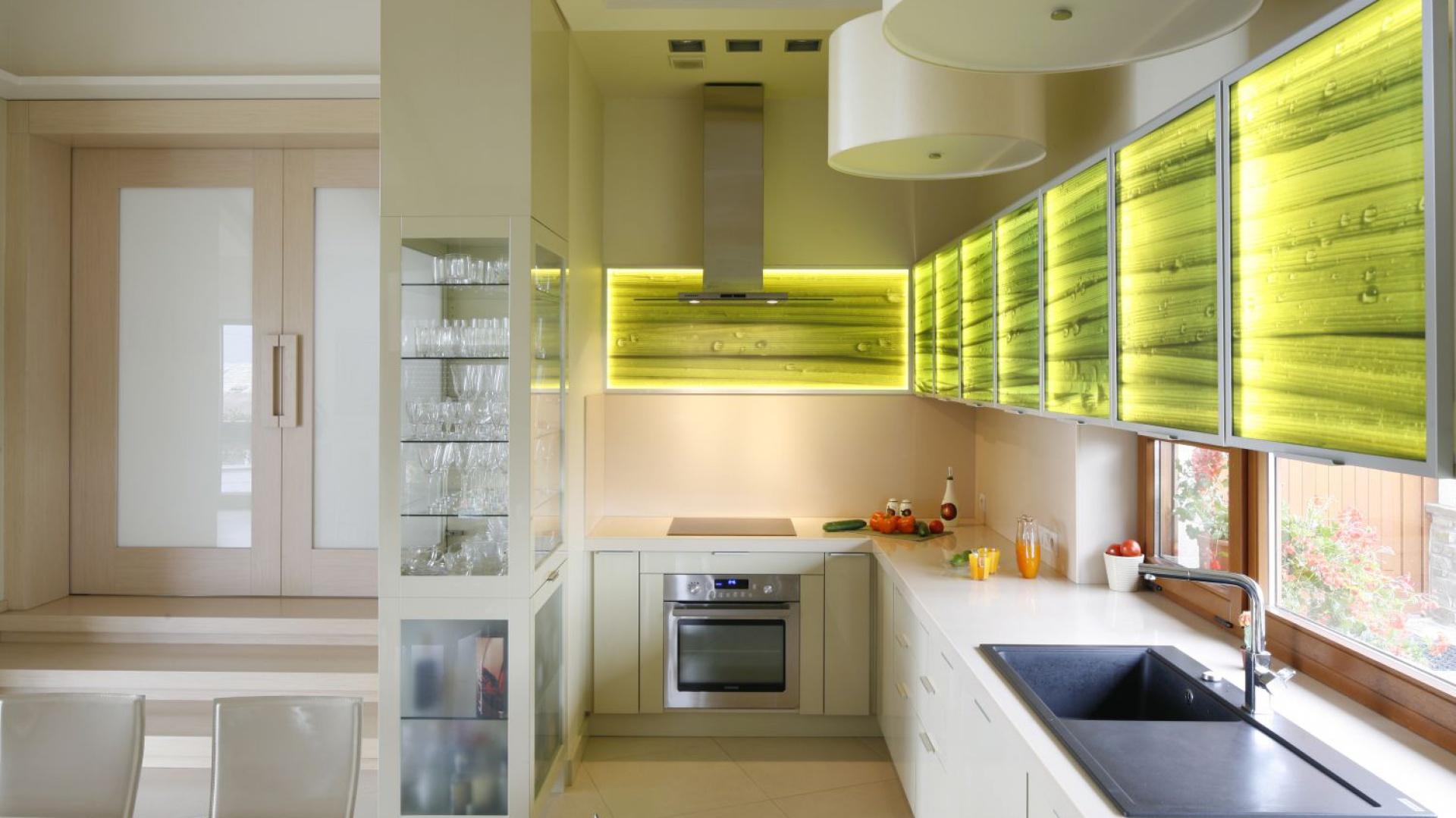 Rząd górnych szafek nadaje tej kuchni świeży, energetyzujący wyraz. Fronty są podświetlone oraz ozdobione grafiką z odświeżająco prezentującą się roślinnością. Projekt: Małgorzata Brewczyńska. Fot. Bartosz Jarosz.