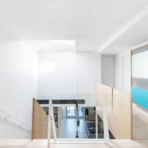Duże połacie bieli, otwarta klatka schodowa prowadząca do przeszklonego sufitu w dachu oraz przeszklone elementy działowe optycznie powiększają i rozświetlają wnętrze. Projekt: Nature Humaine. Fot. Adrien Williams.