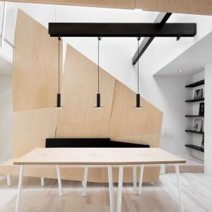Jednym z najciekawszych elementów architektonicznych we wnętrzu jest zabudowa klatki schodowej, funkcjonująca jako element działowy, ale także jako podstawa dla ławy - siedziska przy stole jadalnianym. Projekt: Nature Humaine. Fot. Adrien Williams.