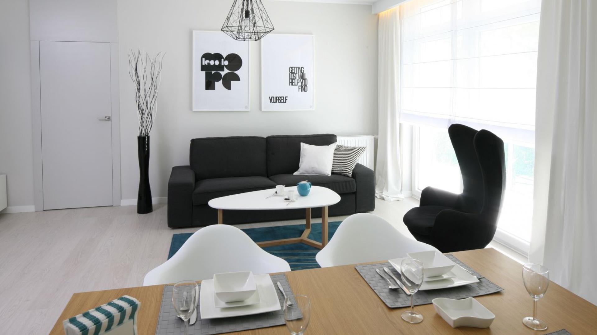 Jasną przestrzeń dzienną urządzono w subtelnych i bardzo modnych szarościach. Strefę wypoczynkową organizuje niewielka sofa w czarnym kolorze. Projekt: Anna Maria Sokołowska. Fot. Bartosz Jarosz.