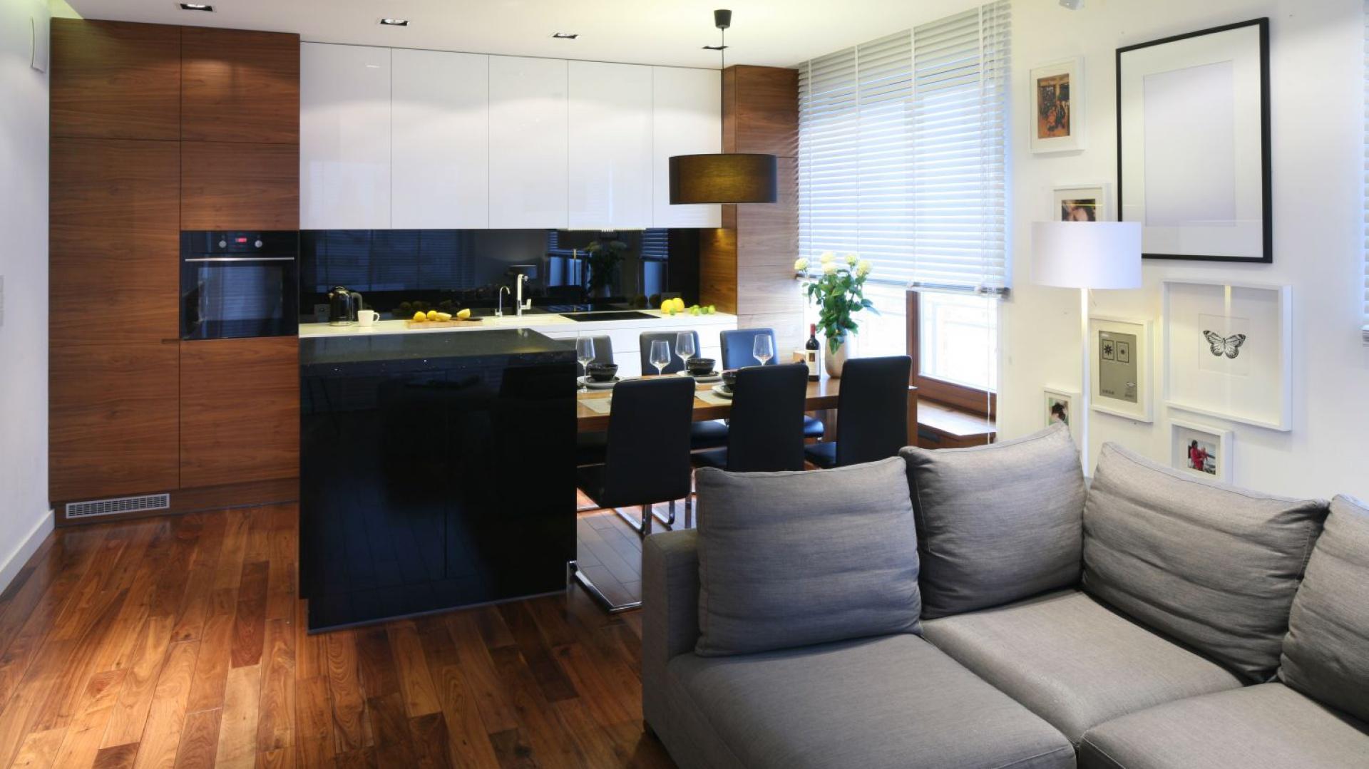 W otwartej kuchni zabudowa kuchenna ulokowana została tylko na jednej ścianie, stanowiąc eleganckie tło dla aranżacji strefy dziennej. Projekt: Agnieszka Ludwinowska. Fot. Bartosz Jarosz.