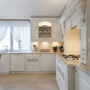 W tej romantycznej, klasycznej kuchni meble zwieńczono blatem w konglomeratu kwarcowego, utrzymanym w barwie, harmonizującej z frontami zabudowy. Krawędzie blatu udekorowano ozdobnym żłobieniem. Fot. Pracownia Mebli Vigo.