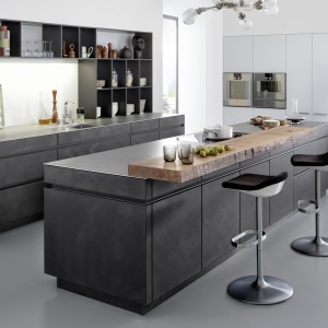 Fronty kuchenne wykonano z płyty drewnianej, wykończonej cieniutką warstwą betonu. Tak niesamowita podstawa została zwieńczona bardzo cienkim blatem ze stali szlachetnej, z dodatkową nakładą w postaci litego drewna. Efekt jest zachwycający! Fot. Leicht, kuchnia Conrete-A.