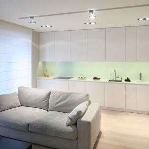 Białe meble kuchenne z gładkimi połyskującymi frontami odbijają światło i dodają pomieszczeniu głębi. Projekt: Monika i Adam Bronikowscy. Fot. Bartosz Jarosz.