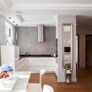 Małą kuchnię urządzono we wnęce, otwartej na salon i jadalnię. Jasne kolory zastosowane w aranżacji pomieszczenia powiększają je optycznie. Projekt: Arkadiusz Grzędzicki. Fot. Adam Ościłowski, www.panadam.pl.
