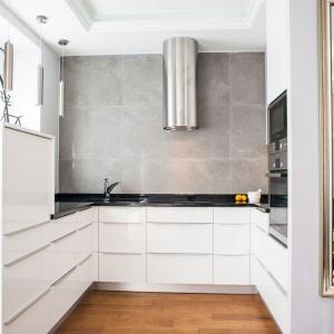 Białe fronty wykonane w wysokim połysku odbijają światło i dodają tej małej kuchni głębi. Projekt: Arkadiusz Grzędzicki. Fot. Adam Ościłowski, www.panadam.pl.