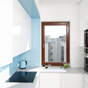 Białe meble kuchenne optycznie powiększają wnętrze. Zastosowanie wysokiego słupka zabudowy, w którym zamontowano sprzęt AGD, pozwoliło uporządkować przestrzeń. Projekt: Agnieszka Zaremba, Magdalena Kostrzewa-Świątek. Fot. Bartosz Jarosz.