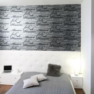 W sypialni głównym motywem dekoracyjnym jest tapeta ze zmysłowym napisem utrzymana w szarej palecie barw. To jednak nie jedyne elementy zdobnicze utrzymane w tej modnej kolorystyce. Projekt: Magdalena Smyk.  Fot. Bartosz Jarosz.