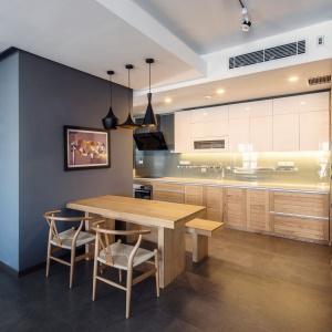 Kuchnia częściowo chowa się za elementem konstrukcyjnym, w których urządzono łazienkę, częściowo przesłania ją stół jadalniany. Zabudowa kuchenna to połączenie drewna na frontach dolnych szafek oraz bieli w wysokim połysku na górze. Projekt: Le Studio. Fot. Thien Thach.