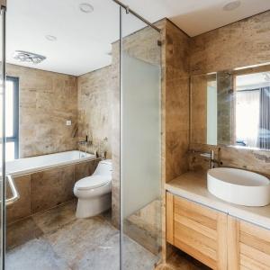 W łazience postawiono na ciepłe, przyjazne kolory. Dominuje tutaj beż oraz drewno, budujące w pomieszczeniu atmosferę salonu SPA. Projekt: Le Studio. Fot. Thien Thach.