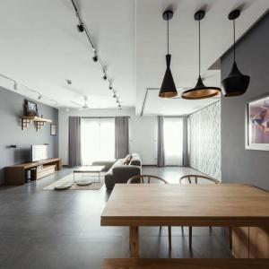 Nowoczesne wnętrze urządzono w modnych kolorach. Dominuje tutaj szarość w różnych odcieniach, a chłodną aranżację ociepla naturalne drewno. Projekt: Le Studio. Fot. Thien Thach.