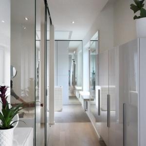 Przechodzący przez korytarz goście mogą poczuć się przez chwilę jakby przebywali w pokoju luster. Szafa wyłożona frontami na wysoki połysk i wysokie tafle szkła obijają swoje kształty, budując przestronność holu. Projekt: Soma Architekci. Fot. Soma Architekci.