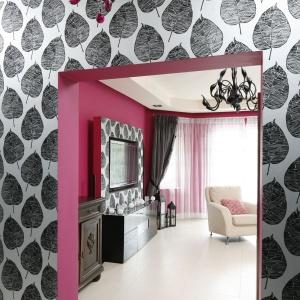 """Nawiązaniem do salonu jest wykorzystanie tej samej, idealnie pasującej do fuksjowego wnętrza """"liścistej"""", srebrnej tapety znajdującej się również w przedpokoju."""